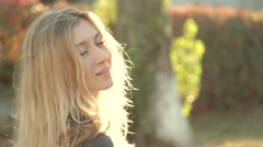 Beautiful girl smiling at the camera in bright afternoon sun Stock Footage