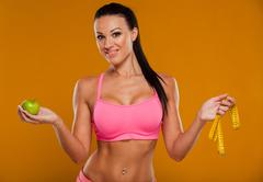 Young sport woman body measuring waist with tape measure and green apple - stock photo