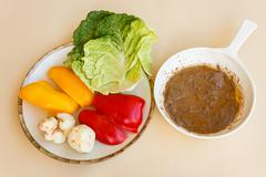 pan of bagna cauda with a dish of vegetables as trimming - stock photo