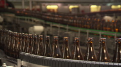 Row of bottles of beer on conveyor belt (background out of focus) Stock Footage