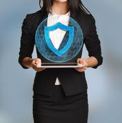 Beautiful girl holding a tablet with digital network globe and shield icon - stock photo