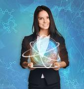 Beautiful girl holding a tablet with digital globe - stock photo