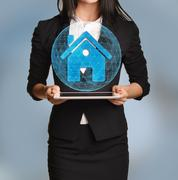 Beautiful girl holding a tablet with digital network globe and home icon - stock photo