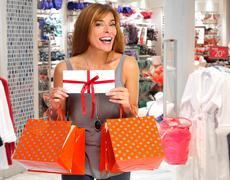 Shopping woman with envelope and gifts. Stock Photos