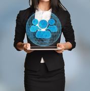 Beautiful girl holding a tablet with digital network globe and team icon Stock Photos