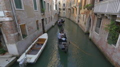 Paddling gondolas on a small canal in Venice Stock Footage