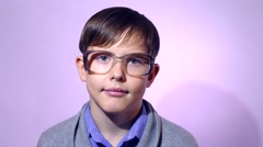 Portrait of boy teenager schoolboy nerd glasses on purple background education Stock Footage
