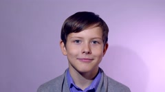 Teenage boy smiling portrait on a purple studio background Stock Footage