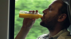 Young man drinking orange juice during train ride, slow motion, shot at 240fps Stock Footage