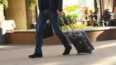Man on a business trip mission roll behind a suitcase on wheels Stock Footage