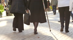 Old age senior people with cane walk in a pedestrian street city center - stock footage