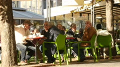 People rest at a street cafe tables in city public pedestrian center of Sofia Stock Footage