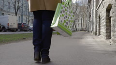 Woman walking in the city and carrying shopping bag Stock Footage