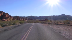 Driving USA: Point of view car in Valley of Fire, Nevada, extreme lens flares Stock Footage