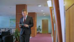 Businessman in a strict suit goes along the corridor and holds the tablet Stock Footage