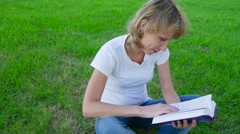 Young woman sitting on the grass and reading a book. Tracking shot. Stock Footage