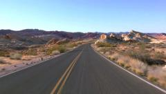 Driving USA: Car driving along empty desert road through Valley of Fire, Nevada Stock Footage