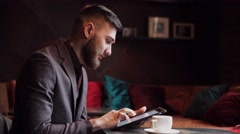 Nerd hipster guy sitting at bar table and using a tablet Stock Footage