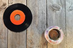Old vinyl record and cup of coffee on a wooden table Kuvituskuvat