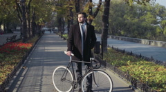young businessman standing on a city alley with bicycle - stock footage