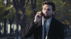 Hansome businessman talking on the phone in the park Stock Footage