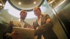 businessman and businesswoman go in the elevator and read news in the tablet - stock footage