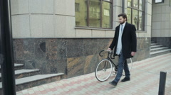 Stock Video Footage of handsome businessman walking with his bicycle in downtown