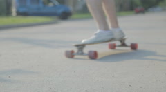 Rider passing by camera on a long board in quiet road - stock footage