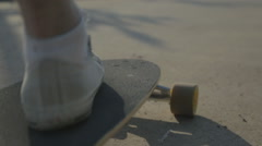 Close up shot. Close up on feet of rider setting long board and rides away - stock footage