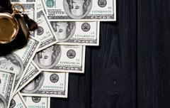 Stack of money dollars laid out like a ladder with antique gold watch on blac Stock Photos
