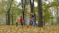 Hyperactive children throwing fallen yellow leaves in the park,kids playing Stock Footage