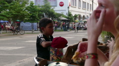 Little boy trying to sell candy in the street - stock footage