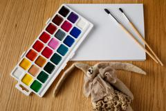 Paints with brush on table with felt cozy doll Stock Photos