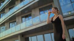 lovely girl costs on a balcony, looks at sunset and drinks champagne. - stock footage