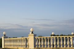Decorative fence of columns on promenade on background of blue sky and clouds Stock Photos