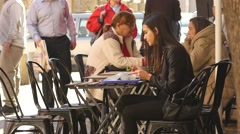 Young brunette woman eating fas food at a public street cafe table Stock Footage
