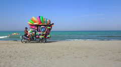 The man ride mobile shop selling toys to child on the beach Stock Footage