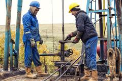 Oil workers check oil pump. Roustabouts doing dirty and dangerous work on an oil - stock photo