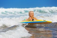Little child swimming with bodyboard on the sea waves - stock photo