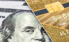 Mastercard Debit Card with US dollar bills Stock Photos