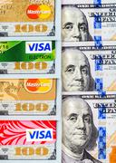 Visa and MasterCard, credit, debit and electronic with US dollar bills Stock Photos