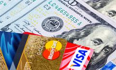Credit cards, Visa and MasterCard, with US dollar bills - stock photo