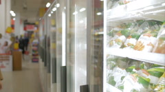 Woman taking frozen product in the shop fridge Stock Footage