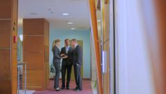 Three young businesspeople cost in the office centre in a corridor - stock footage