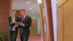 Two colleagues go along the corridor, look in the tablet and discuss the work. Stock Footage