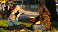 Stock Video Footage of Smoking cigarette teen girls communicate sitting on a grass in a park