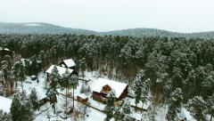 Aerial flight over holiday chalets among the snow-capped trees. Stock Footage
