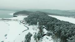 Aerial flight over frozen lake and holiday chalets among the snow-capped trees. - stock footage