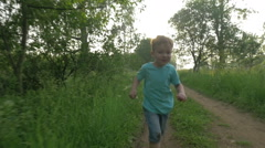 Happy child running in the woods at sunset Stock Footage