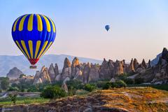 Cappadocia hot air balloon flying over bizarre rock landscape in Turkey Stock Photos